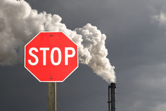 Stop Smokestack Pollution. Stop sign in front of smokestack pollution with dark cloud in the background Stock Images