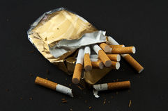 Stop Smoking!. Broken crushed pack of cigarettes on the black background Stock Photos