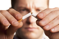 Stop smoking. Serious man with a blurred face breaks a cigarette Royalty Free Stock Image