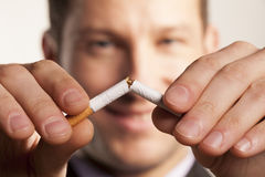 Stop smoking. Smiling man with a blurred face breaks a cigarette stock photography