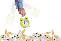 Stop smoking concept. Alarm clock and bunch of broken cigarettes Stock Images