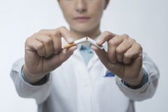 Stop smoking. Concept with female doctor breaking a cigarette Royalty Free Stock Photo