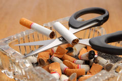 Stop smoking, quit smoking. Scissors cut a cigarette on ashtray, stop smoking concept Stock Image