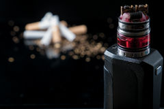 Electronic cigarette with pile of tobacco smokes stock images
