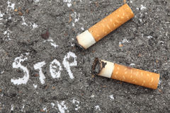 Stop Smoking!. Unhealthy habit. Cigarette butts on ash background with word: Stop. Conceptual image. Close-up stock photos