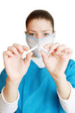 Stop Smoking!. Young female doctor wearing a blue coat and a mask holds a broken cigarette isolated on white. Doctors advice is to quit smoking Stock Photography