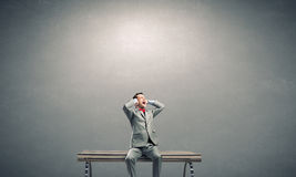 Stop this sound. Frustrated businessman on bench closing ears with hands royalty free stock images