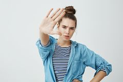 Stop taking pictures of me. Portrait of annoyed angry european woman in fashionable clothes pulling hand towards camera Royalty Free Stock Photos