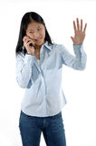 Stop Talking. Young Asian girl talking on a cellphone withwith hand raised royalty free stock images