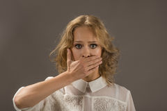 Stop talking!. Pretty woman covering her mouth over gray background. Human emotion face expression Stock Image