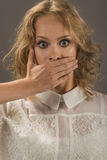 Stop talking!. Pretty woman covering her mouth over gray background. Human emotion face expression Royalty Free Stock Photos