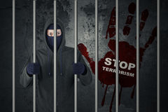 Stop terrorism concept with terrorist in jail. Concept of stop terrorism: Male terrorist standing in the jail while wearing mask royalty free stock image