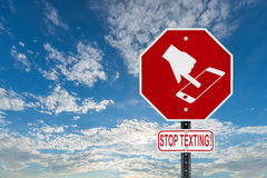 Stop Texting Icon Sign - Blue Sky with Clouds. A red stop sign with a symbol of a hand texting on handheld smartphone device and the words stop texting written stock photography