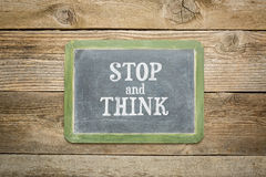 Stop and think text blackboard. Stop and think  text on  a slate blackboard against rustic weathered wood planks Stock Photography
