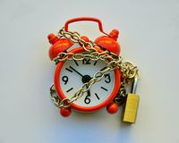 Stop the time concept. Ual image with an alarm clock and a chain with a locker Stock Photos