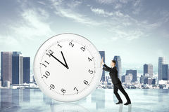 Stop timing concept with businessman pushing big clock at city b Royalty Free Stock Images