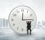 Stop timing concept with businessman trying to stop the time at Royalty Free Stock Images