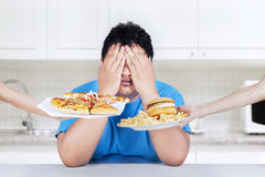 Stop to eat junk food. Fat man rejecting to eat junk food. Shoot at home in the kitchen royalty free stock photography