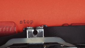 Stop - typed on a old vintage typewriter. Printed on red paper. The red paper is inserted into the typewriter stock video footage