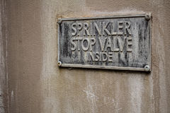 Stop Valve. Old weathered sprinkler stop valve plaque on building Stock Photos