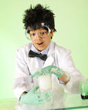 Stop Vaporizing!. A young mad scientist in protective gear attempting to stop a solution from vaporizing in the beaker he's holding Royalty Free Stock Photo
