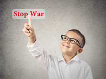 Stop war. Closeup portrait happy, smiling child touching red button, icon stop war on touchscreen display, isolated grey background. Positive face expression Stock Photography