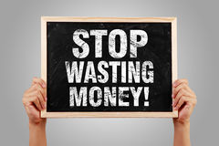 Stop Wasting Money. Blackboard is holden by hands with gray background Royalty Free Stock Images