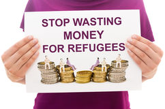 Stop wasting money for refugees. Girl holding white paper sheet with text Stop wasting money for refugees Stock Photo