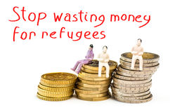 Stop wasting money for refugees. Stacks chart of gold coins isolated on white background with miniature and text Stop wasting money for refugees Stock Images