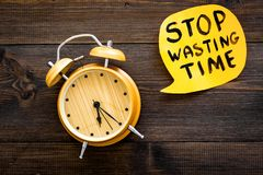 Stop wasting time hand letterng in cloud near alarm clock on dark wooden background top view copy space. Business. Concept, motivation stock images