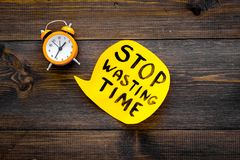 Stop wasting time hand letterng in cloud near alarm clock on dark wooden background top view space for text. Business. Stop wasting time hand letterng in cloud stock images