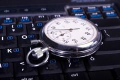 Stop-watch. Close-up stop-watch laying down the laptop kayboard Royalty Free Stock Photos