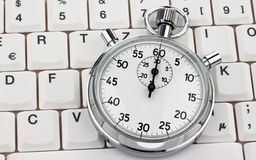 Stop watch on computer keyboard Stock Photo