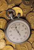 Stop watch on heaped of gold coins Royalty Free Stock Photo