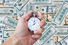 Stop watch over money background. Woman's hand holding a stop/production watch over money background Stock Photo