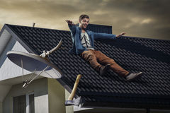 Stop watching Tv. Young crazy happy man sliding down off the roof. He chopped off satellite Tv antenna with an axe. Breaking the habit- no more watching Tv at Royalty Free Stock Photography