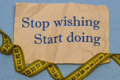 Stop wishing, start doing! Motivational phrase on a sheet of pap Royalty Free Stock Images