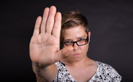 STOP. Woman against black background tries to stop something or someone stock image