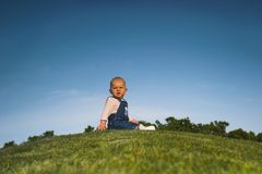 Stop the world - I want to get off. Baby is sitting on a hill, looking back and makes a scared face like someone who has enough of something Royalty Free Stock Images