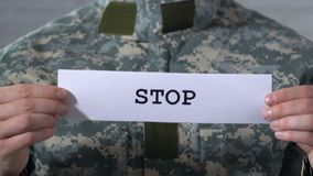 Stop written on paper in hands of soldier, concept of ending war, world peace. Stock footage stock footage