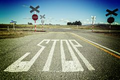 New Zealand Uncontrolled Level Crossing. Stop written on road at level crossing - uncontrolled level crossing in rural Canterbury, New Zealand Royalty Free Stock Image