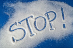 STOP written with sugar. Sugar on a blue background with warning message STOP written on it. Health concept. Diabetes hazard Royalty Free Stock Images