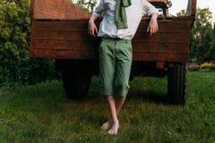 Stopa nad zieloną trawą nadzy cieki stać na zielonej trawie facet w białej koszula z zielonym pulowerem w zielonych skrótach i zb zdjęcie stock