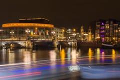 Stopera και μπλε γέφυρα που διασχίζουν τον ποταμό Amstel τη νύχτα στο τ στοκ φωτογραφίες