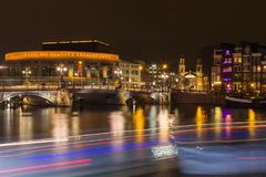 Stopera and Blue Bridge crossing the Amstel river at night in t stock photos
