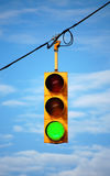 Stoplight on green. Suspended stoplight showing green, with sky background royalty free stock images