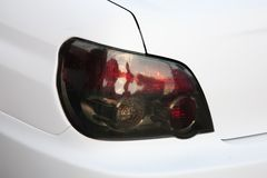 Stoplight of white car. Closeup of Stoplight of modern white car royalty free stock photography