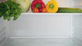 Stopmotion from the start of The empty shelves Of. Refrigerator to filling them useful products, vegetables, dairy, fruits, bread, greens. HD. 1920x1080 stock video footage