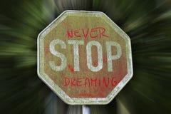 Stoppa aldrig att drömma meddelandet på trafiktecken Royaltyfria Bilder