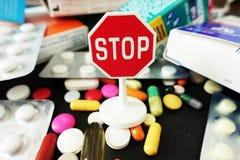 Stoppa antibiotikummar eller läkarbehandlingöverskottsen med färgrika läkemedeldroger med stopptecknet överst royaltyfri bild